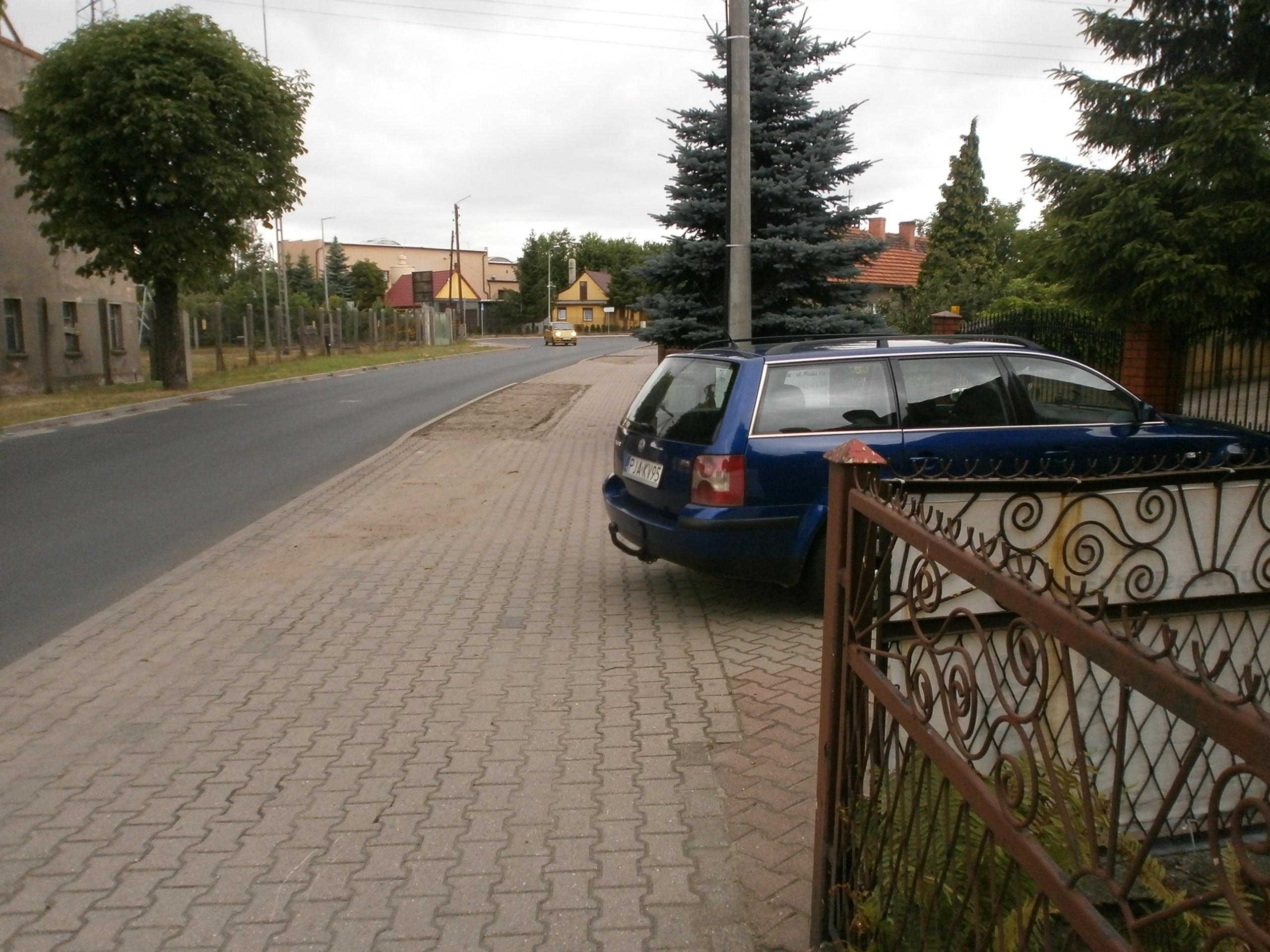 Samochów parkujący częściowo na chodniku