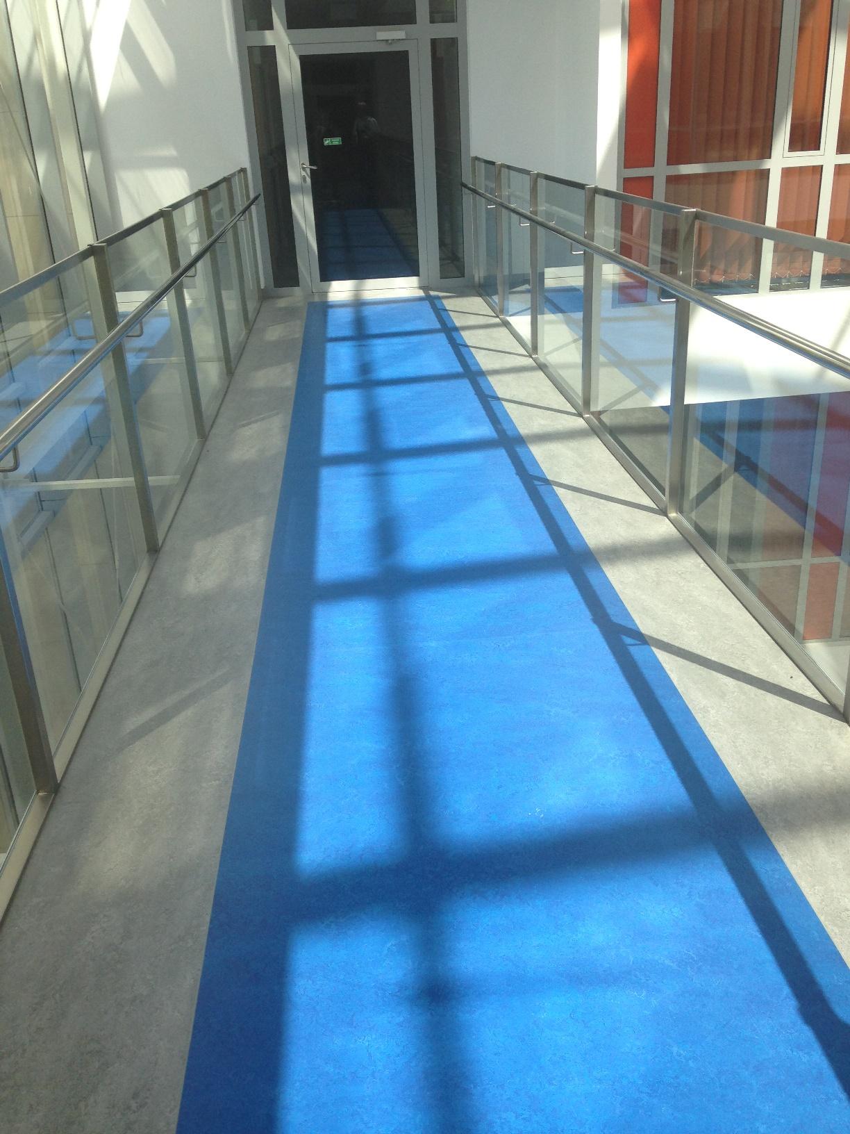 2 piętro - korytarz (mostek łączący skrzydła budynku) z wyodrębnionym kontrastowo traktem komunikacyjnym
