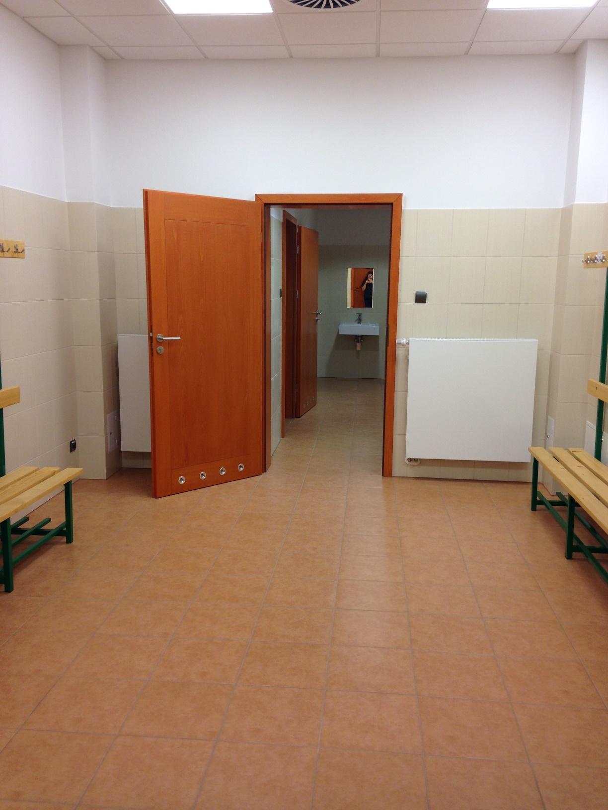 Przebieralnia damska - szatnia z widocznymi na wprost drzwiami prowadzącymi do pomieszczenia toalet i natrysków